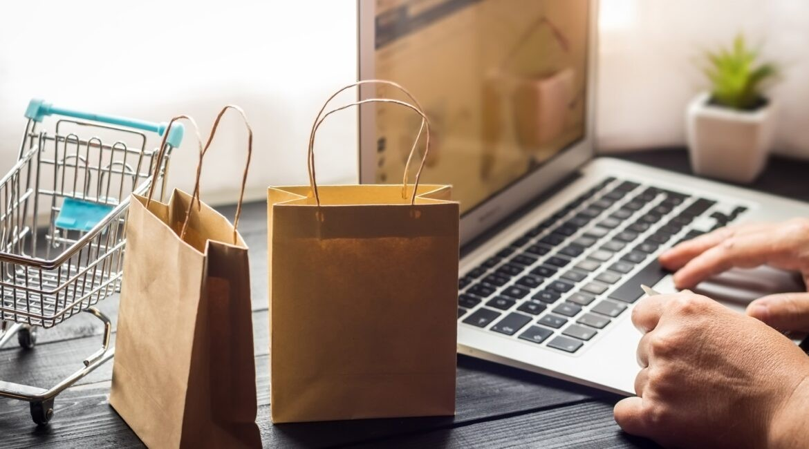 laptop on desk with paper bags
